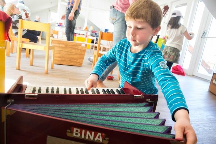Zu sehen ist ein ca. 6-jähriger Junge. Vor ihm auf dem Boden liegt ein Akkordeon. Er zieht es mit einer Hand auseinander, mit der anderen Hand drückt er eine Taste auf der Klaviatur.