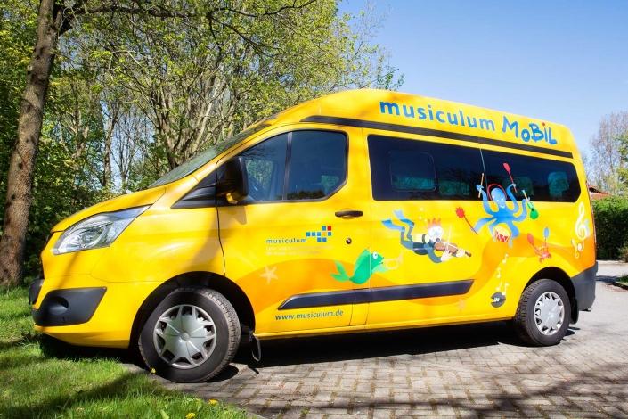 Zu sehen ist das musiculum MOBIL. Ein gelber Ford Transit der mit bunten maritimen Motiven und mit Musiknoten bedruckt ist.